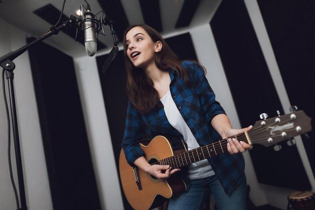 Mädchen nimmt ein lied in einem modernen tonstudio auf. Premium Fotos
