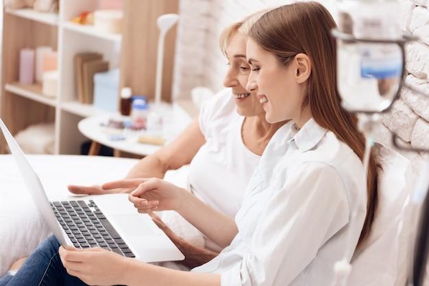 Mädchen pflegt ältere frau mit computer zu hause Premium Fotos
