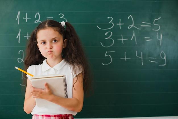 Mädchen posiert mit notizblock in mathe-klasse Kostenlose Fotos