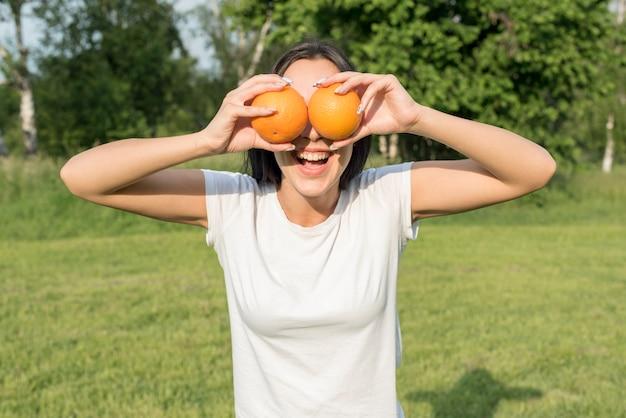 Mädchen posiert mit zwei orangen Kostenlose Fotos