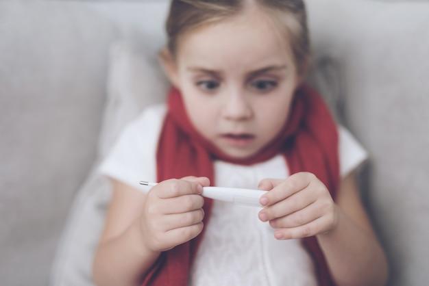 Mädchen schaut auf das thermometer, es hat eine hohe temperatur Premium Fotos