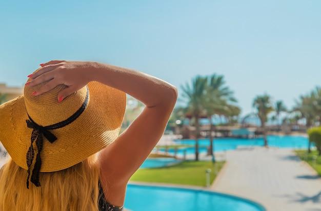 Mädchen schaut auf den pool und das meer Premium Fotos