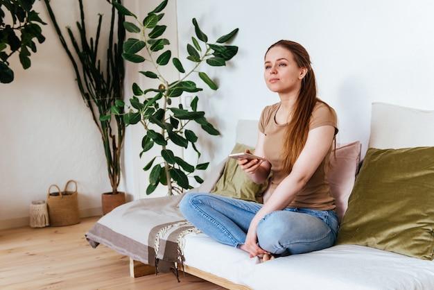 Mädchen schaut voraus, das auf dem sofa zu hause mit smartphone sitzt Premium Fotos