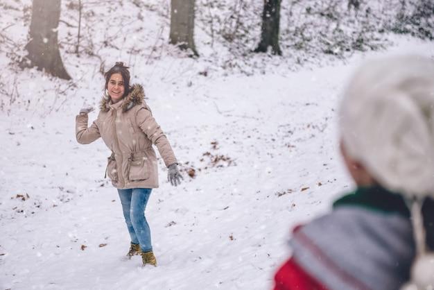 Mädchen schneeball werfen Premium Fotos
