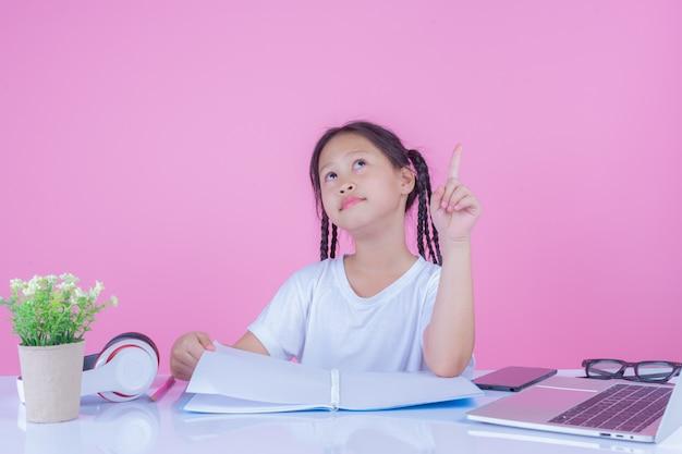 Mädchen schreiben bücher auf einem rosa hintergrund. Kostenlose Fotos