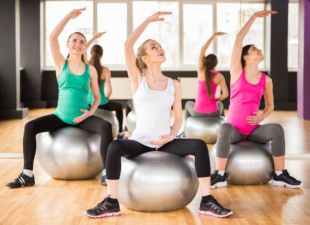 Mädchen sitzen auf bällen und trainieren. Premium Fotos