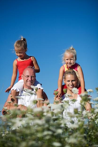 Mädchen sitzen auf den schultern ihrer eltern Premium Fotos