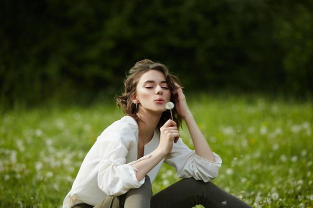 Mädchen sitzen in einem feld auf dem frühlingsgras mit löwenzahnblüten Premium Fotos