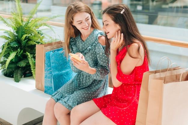 Mädchen sitzen und reden im einkaufszentrum Kostenlose Fotos