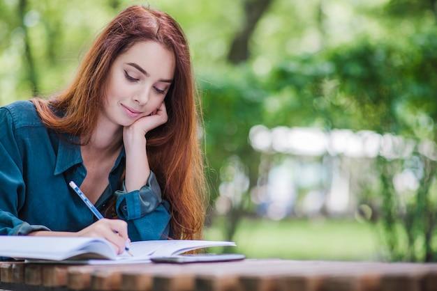 Mädchen sitzt am tisch schriftlich Kostenlose Fotos