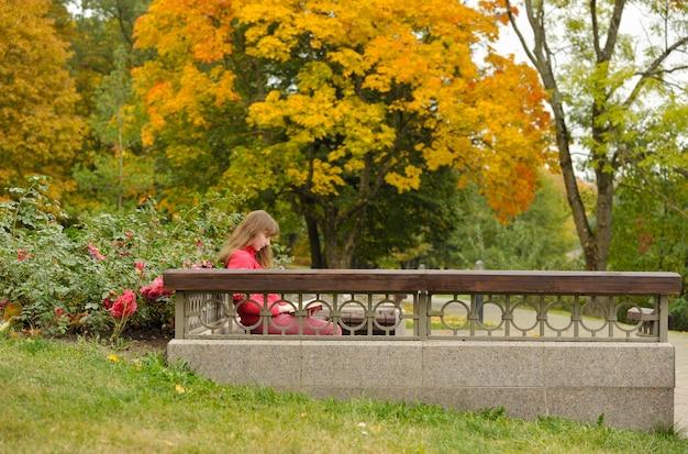 Mädchen sitzt auf bank und lesebuch, herbst. Premium Fotos