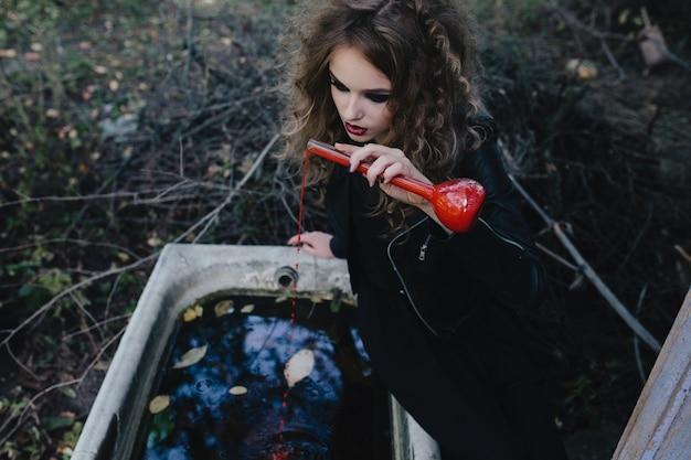 Mädchen sitzt auf dem rand einer badewanne mit einem roten trank Kostenlose Fotos