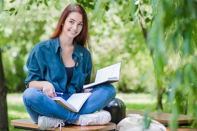 Mädchen sitzt auf dem tisch mit lehrbuch lächelnd Kostenlose Fotos