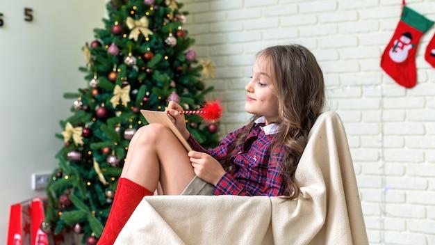 Mädchen sitzt auf einem stuhl und schreibt zu hause einen brief, weihnachtsbaum an der wand Premium Fotos