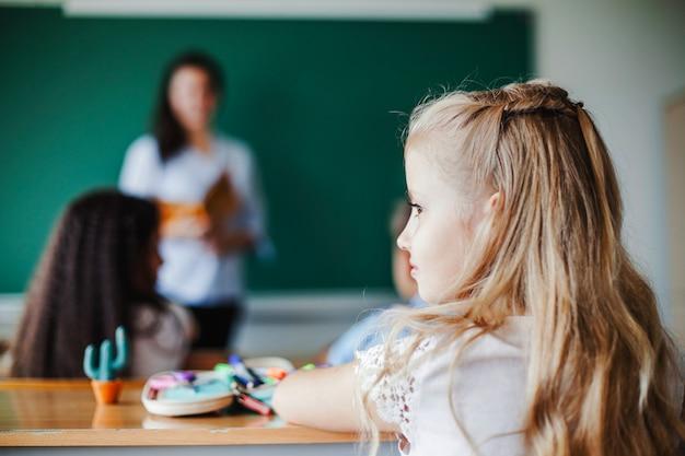 Mädchen sitzt im klassenzimmer Kostenlose Fotos