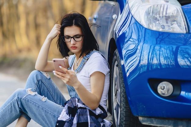 Mädchen sitzt neben kaputtem auto mit offener motorhaube und spricht telefonisch Premium Fotos