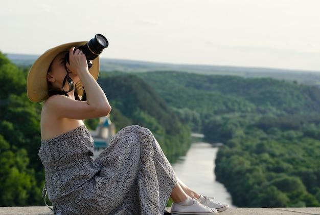 Mädchen sitzt und macht fotos vor dem hintergrund des waldes und des sich schlängelnden flusses Premium Fotos