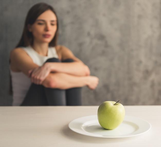 Mädchen sitzt vor dem teller mit einem apfel. Premium Fotos