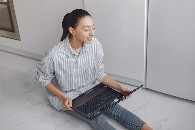 Mädchen sitzt zu hause und benutzt den laptop Kostenlose Fotos
