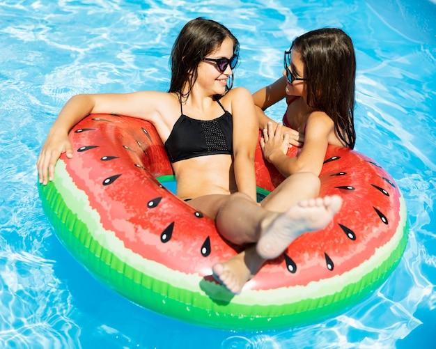 Mädchen spielen im schwimmbad Kostenlose Fotos