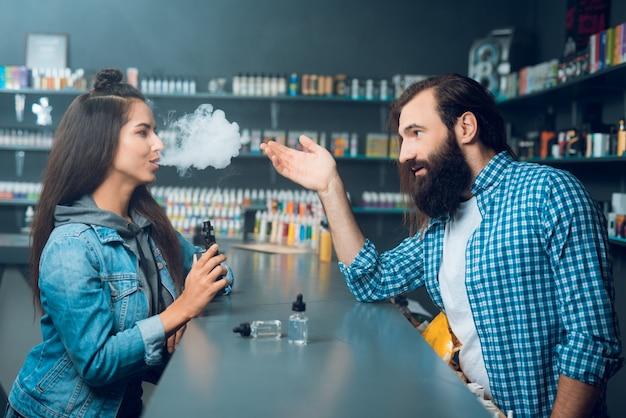 Mädchen spricht mit dem großen mann des verkäufers mit dem langen haar und einem bart. Premium Fotos