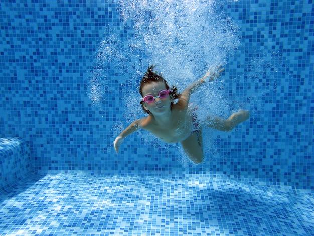 Mädchen springt und schwimmt im pool unter wasser Premium Fotos