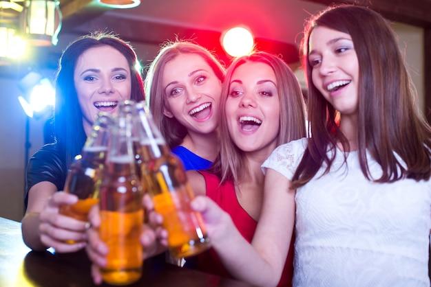 Mädchen stossen im club mit bier an. Premium Fotos