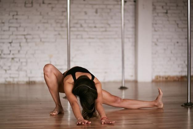 Mädchen tut das ausdehnen ihres rückens und der beine vor einem training in der stangentanzgymnastik Kostenlose Fotos