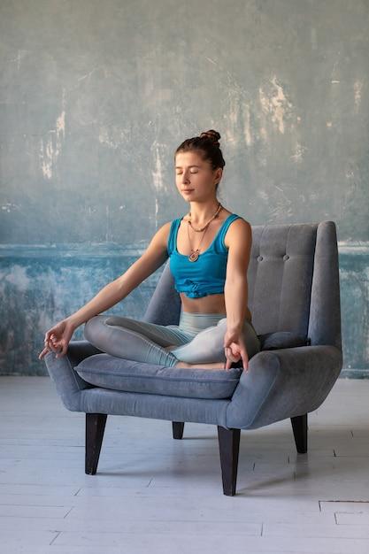 Mädchen üben yoga, während auf sessel mit lotos pose gekreuzte beine sitzen. Premium Fotos