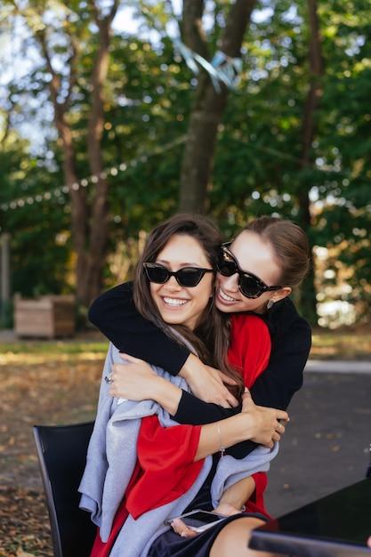 Mädchen umarmt ihre freundin. porträt zwei freundinnen im park. Kostenlose Fotos