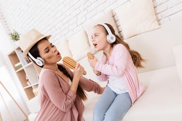 Mädchen und frau in den kopfhörern zu hause singend. Premium Fotos