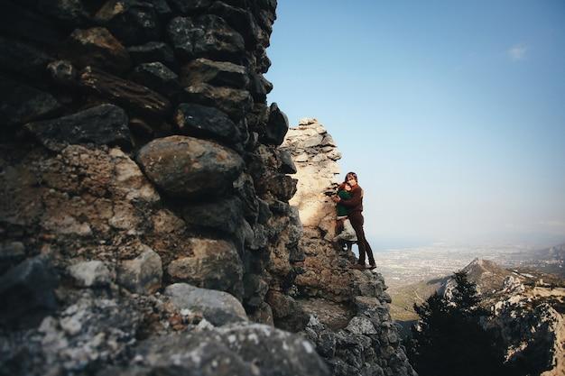 Mädchen und ihr freund umarmen sich und lehnen sich an den felsen in der landschaft Kostenlose Fotos