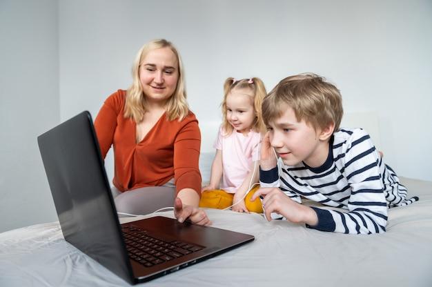 Mädchen und junge mit laptop und kopfhörer zu hause mit mutter Premium Fotos