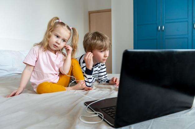 Mädchen und junge mit laptop und kopfhörer zu hause Premium Fotos