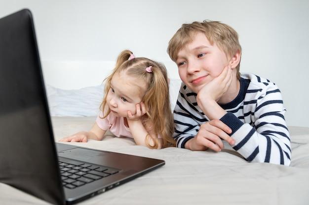 Mädchen und junge mit laptop zu hause Premium Fotos