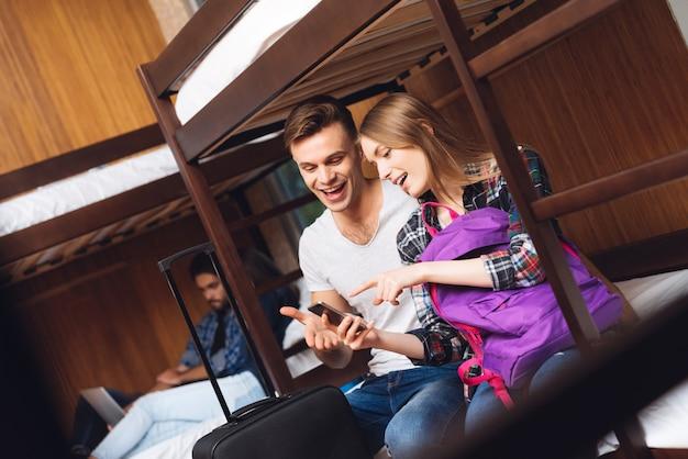 Mädchen und mann schauen telefon an und lachen zusammen. Premium Fotos