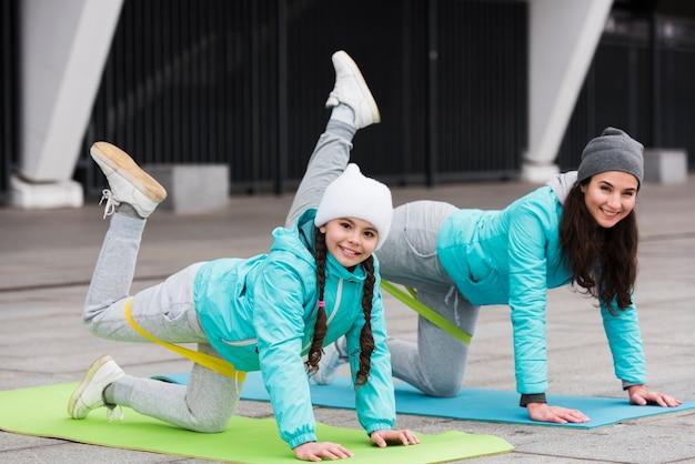 Mädchen und mutter trainieren mit gummibändern auf matte Kostenlose Fotos