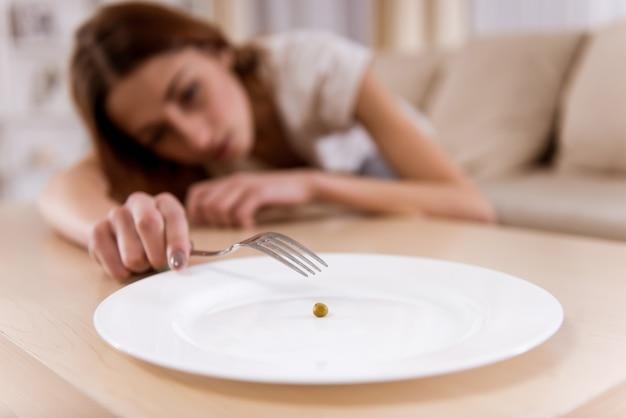 Mädchen von unterernährung erschöpft liegt auf dem sofa. Premium Fotos