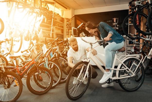 Mädchen wählt stadtfahrrad mit verkäufer im sportspeicher. Premium Fotos