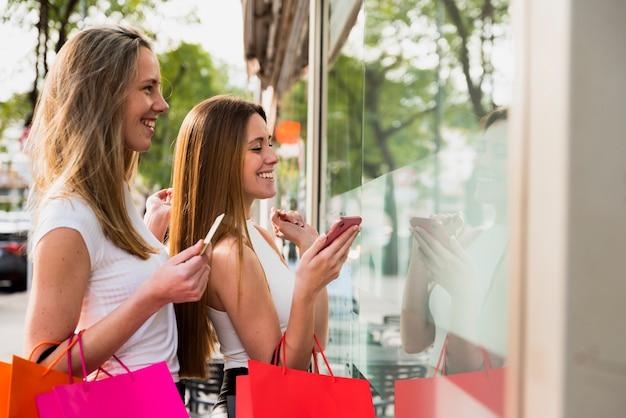 Mädchen, welche die einkaufstaschen betrachten schaufenster halten Kostenlose Fotos