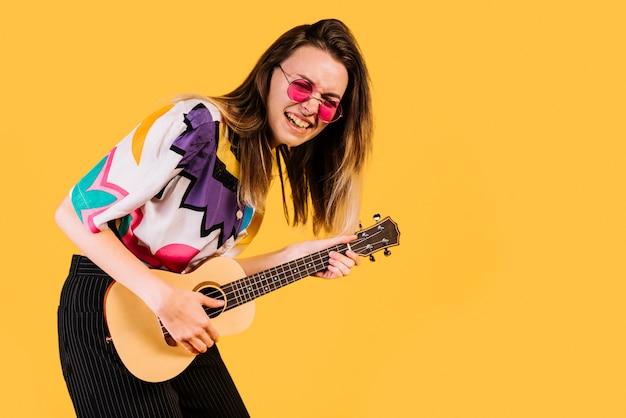 Mädchen, welches die ukulele spielt Kostenlose Fotos