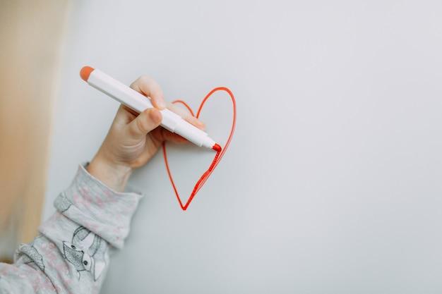 Mädchen zeichnet herz mit markierung auf einer weißen tafel. muttertag. valentinstag Premium Fotos