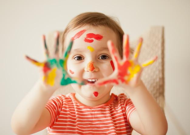 Mädchen zeigt gemalte hände. hände in bunten farben gemalt. bildungs-, schul-, kunst- und malkonzept. Premium Fotos