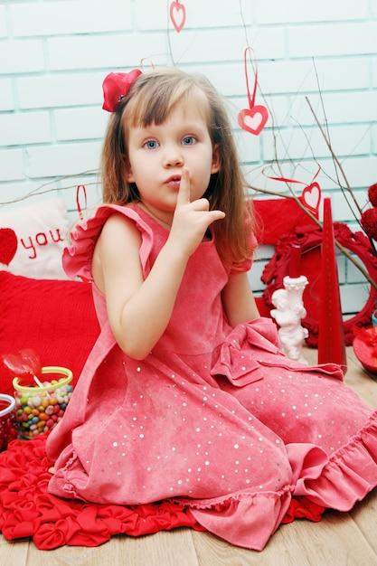 Mädchen zeigt leise geste und bereitet eine überraschung vor Premium Fotos