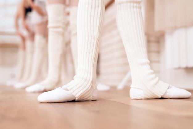 Mädchen ziehen weiße strumpfhosen und ballettschuhe an. Premium Fotos