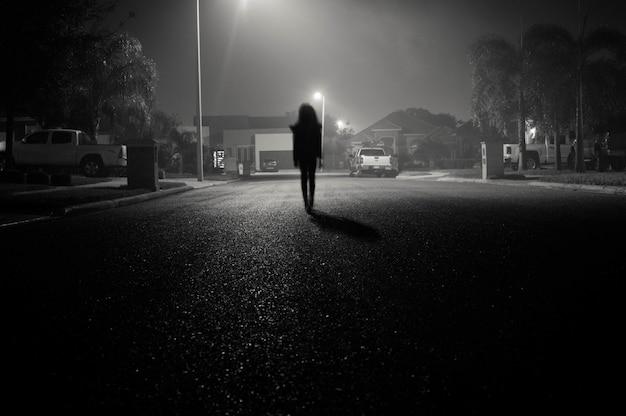 Mädchen zu fuß in einer städtischen straße in der nacht unter straßenlaternen Kostenlose Fotos