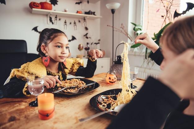 Mädchen zwei im kostüm, das zu mittag isst Premium Fotos