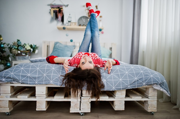 Mädchenabnutzung auf winterstrickjackebett auf raum mit weihnachtsbaum. Premium Fotos