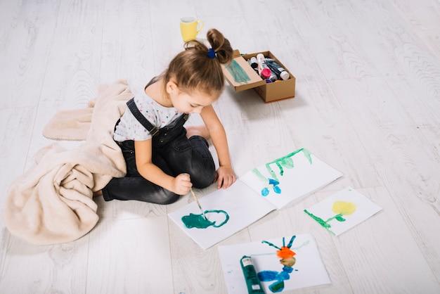 Mädchenanstrich durch wasserfarben auf nahe papierbehälter und sitzen auf fußboden Kostenlose Fotos
