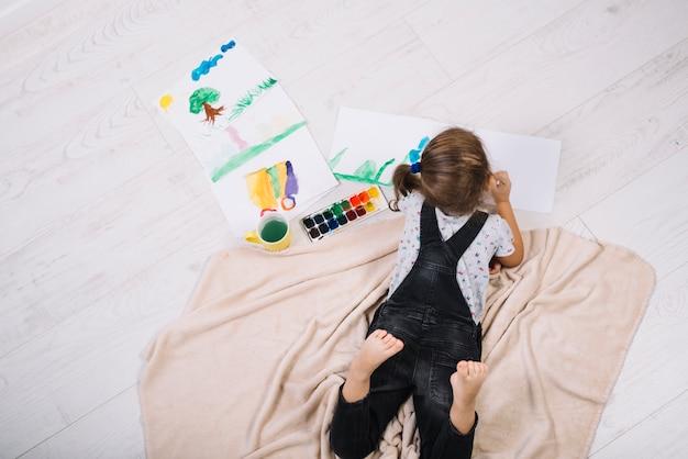 Mädchenanstrich durch wasserfarben auf papier und liegend auf fußboden Kostenlose Fotos